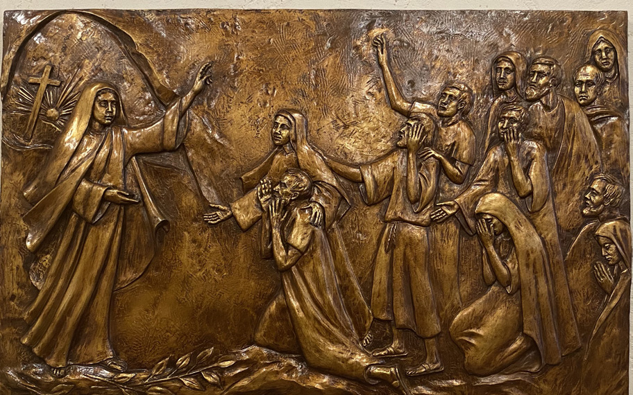 In a rectangular bronze relief, Mary of Magdala walks from Jesus' tomb towards a group of 12 women and men with her arm raised. Some of them kneel and react in astonishment.
